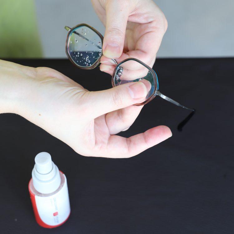 ②メガネクリーナーをレンズに吹きかけ、汚れを浮かすように指で軽くなじませます。